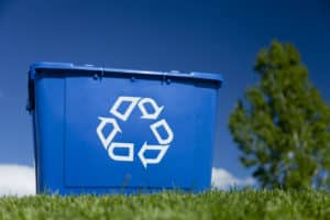 Recycleing bin on grass with sky and tree in the background.